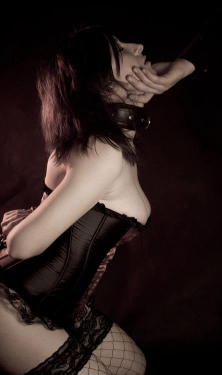 corseted female slave kneeling for master