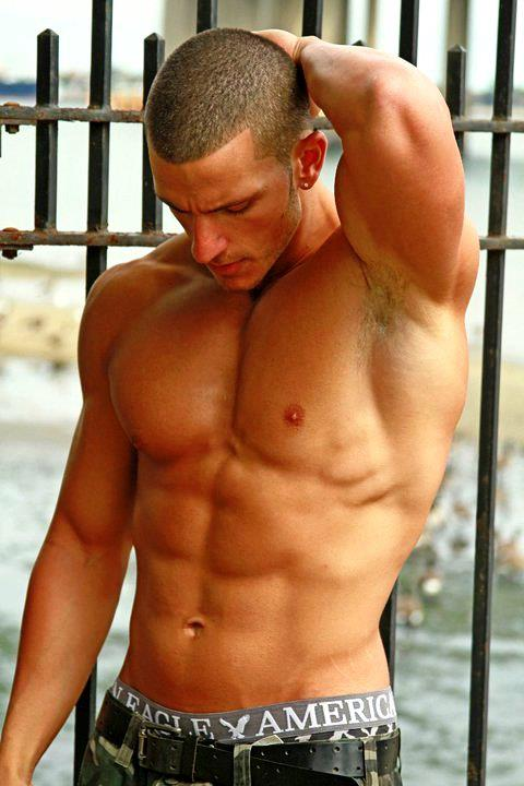 muscular shirtless hunk by the water