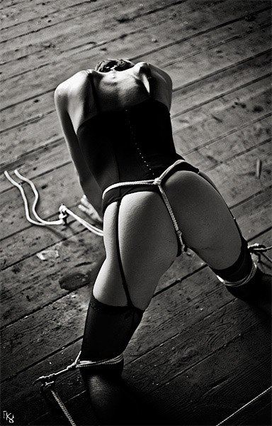 female submissive in stockings and bodice tied to the floor with rope