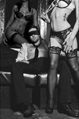 dominant women in stockings and blindfolded slave boy in suit